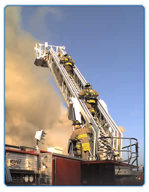 Firefighters climbing a fire ladder with heavy smoke in the background during a fire training in 201